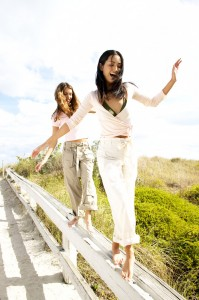 Young Women Smiling Walking on a Railing