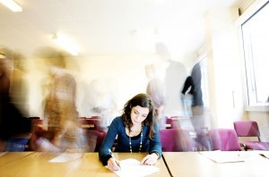 Girl concentrating on writing in blurred room